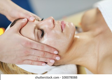 Beautiful young woman in spaand wellness. Face back and  stone massage