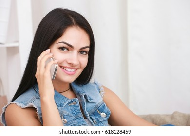 Beautiful young woman speaking by mobile phone indoors.