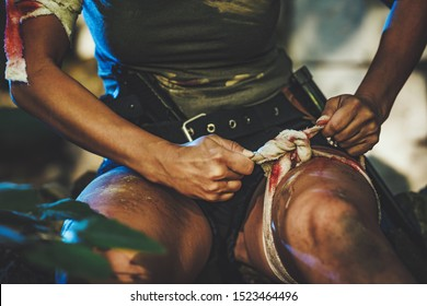 Beautiful young woman special forces wraps a wound on her leg as she is wounded in combat.
