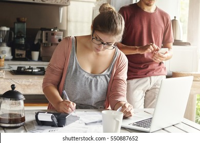 Beautiful young woman in spectacles looking serious writing down with pen while managing taxes and calculating bills, trying to cut domestic expenses to save money and afford to make big purchase