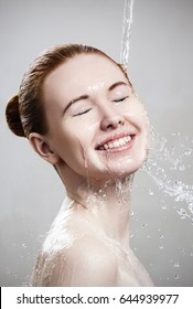 Beautiful young woman in splashes of clear water.