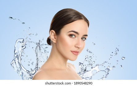 Beautiful young woman and splashing water on light background. Spa portrait