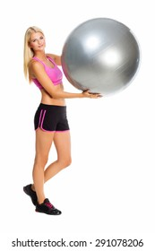 Beautiful young woman in sport wear holding big ball. Isolated over white background.