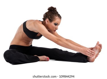 A beautiful young woman in a sports bra and yoga pants performing head to knee Yoga pose isolated on a white background.