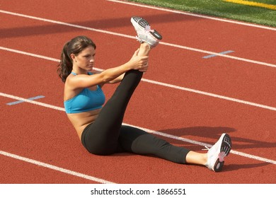 Beautiful Young Woman in Sports Bra Stretching Raised Leg on Running rack