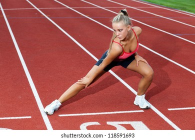 Beautiful young woman in a sports suit doing training exercises before running