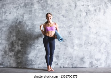 Beautiful young woman in sports wear is holding a yoga mat looking at camera and smiling, standing on a gray background.  After workout.