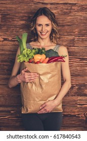 Beautiful young woman in sportswear is holding a shopping bag full of healthy food, looking at camera and smiling, on wooden background