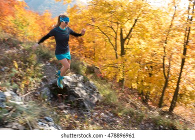 beautiful young woman in sportswear running fast down the hill on autumn trail with colorful trees (panning for movement, sharp face)
