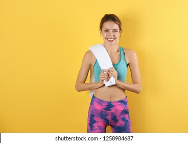 Beautiful young woman in sportswear with towel on color background