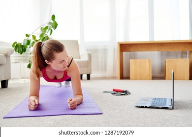 Beautiful young woman in sportwear doing plank exercise in living room at home, watching videos on laptop computer and repeating online instructions by coach, copy space