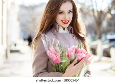 Beautiful young woman with spring tulips flowers bouquet at city street. Happy girl smiling and holding pink tulip flowers outdoors. Spring portrait of pretty female in park.