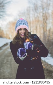 Beautiful young woman with sprinkler, outside in park on snowy winter day, smiling, wearing knitted hat, gloves and coat. Natural lighting, no retouch.