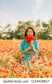 Beautiful young woman standing with bouquet of red poppies in meadow on summer day.