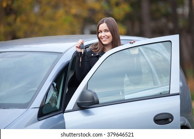 Beautiful young woman standing by the car with car keys