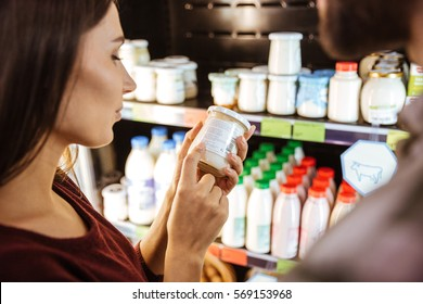Beautiful young woman standing and choosing milk product in grocery store
