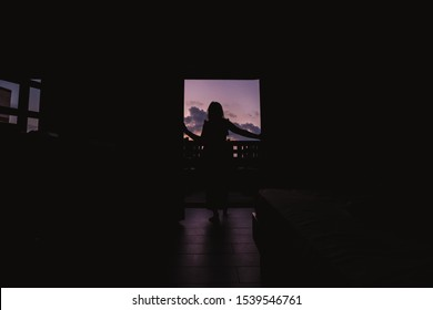 Beautiful young woman standing in doorway at sunset. Silhouette of sensual lady looking at pink sky in twilight. Girl enjoying evening scenery. Female figure in door entrance back view