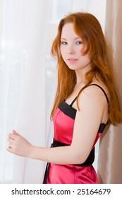 Beautiful young woman standing near a window