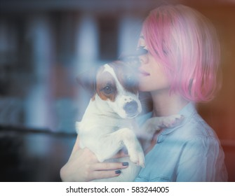 beautiful young woman standing near the window and kissing her dog