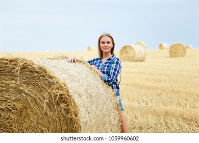 Beautiful young woman standing on field and leaning on roll bale of straw. She is smiling and looking at camera.