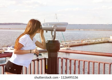 beautiful young woman standing on quay near with telescope and smiling.
