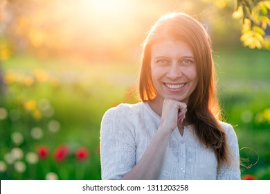 Beautiful young woman  standing on a clearing of green grass with blooming tulips at sunset