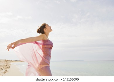 Beautiful young woman standing on a golden beach shore, with a pink fabric sarong around her body and floating with the breeze against a blue sky and sea during a summer vacation break.