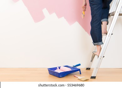 Beautiful young woman standing on ladder doing wall painting. mixed race asian chinese female model