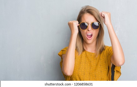 Beautiful young woman standing over grunge grey wall wearing retro sunglasses annoyed and frustrated shouting with anger, crazy and yelling with raised hand, anger concept