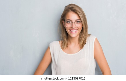 Beautiful young woman standing over grunge grey wall wearing glasses with a happy face standing and smiling with a confident smile showing teeth