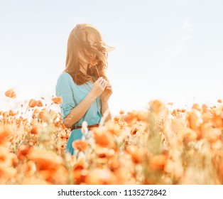 Beautiful young woman standing in poppies meadow and sniffing a flower in summer outdoor.