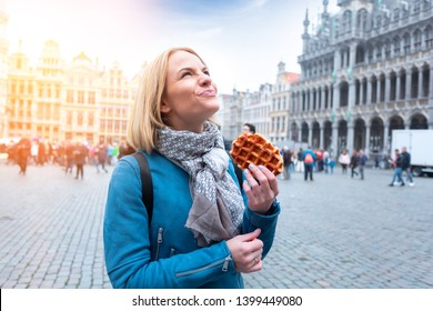 A beautiful young woman is standing in the square in Brussels and is going to eat a delicious waffle - Belgium national sweetness looks up at the sights. Snack on the go.