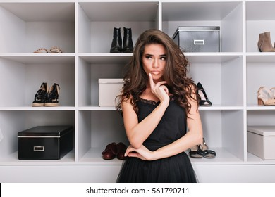 Beautiful young woman standing in a stylish wardrobe, dressing room and thinks what she should wear. She's upset about the choice of clothing. Place for text