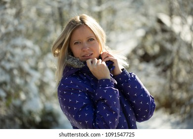Beautiful young woman standing in the winter park, smiling, looking at the camera