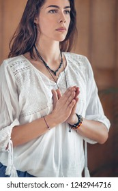 Beautiful young woman standing in a yoga tree pose/Vrikshasana with hands in prayer position.