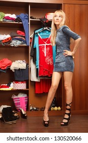 Beautiful young woman stands near her wardrobe  in different shoes and trying to choose