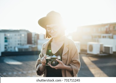 Beautiful young woman stands on top of rooftop in middle of big city with amazing shadows and sun beams and leaks behind her, holds vintage analog camera