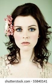 Beautiful young woman stares into the camera. She is wearing a flowery accessory in her hair. Vertical shot.