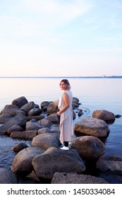 Beautiful Young Woman Staying on Seashore Stones Sunny Day Clean Blue Sky and Calm Slack Sea on Background. Happy Dressed Charming Female in Morning Time Walking on Beach Coastline