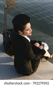 beautiful young woman stewardess in uniform sits on the steps in the park, waiting for her flight