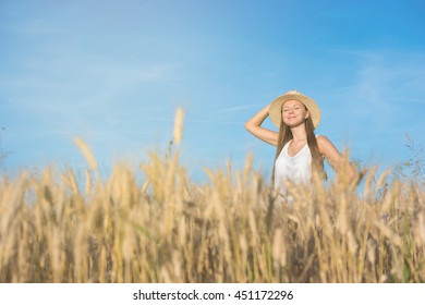 Beautiful young woman in straw hat and white shirt in golden wheat field