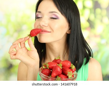 Beautiful young woman with strawberries on natural background