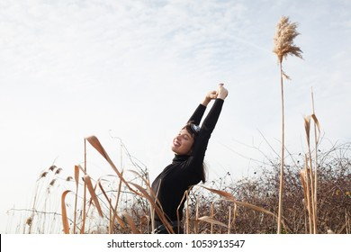 beautiful young woman stretching in dry bush awakening from winter weather