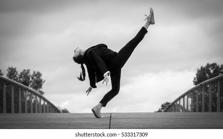 Beautiful young woman in a strict black and white jacket doing contemporary jazz dance moves on a wooden bridge in a modern business district