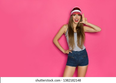 Beautiful young woman in striped shirt, jeans shorts and red sun visor cap holding hand like a pistol and talking. Three quarter length studio shot on pink background.