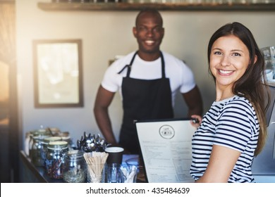 Beautiful young woman in striped shirt with cheerful expression holding menu near young African coffee house owner in apron taking her order