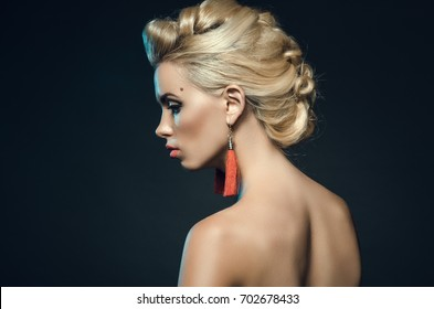 beautiful young woman in studio on a dark background. Fashion portrait of a blonde. the view from the side