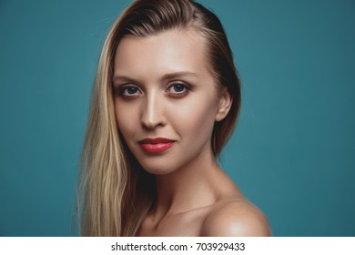 Beautiful young woman studio portrait close up on blue background. Skin care and beauty concept. Classic make up. Long blond hair girl .