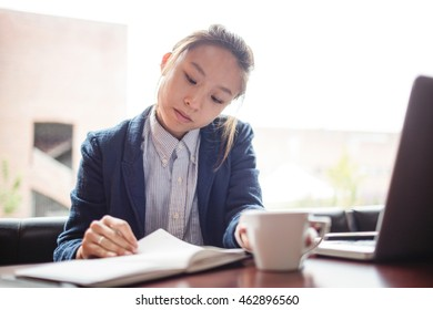 Beautiful young woman studying in college