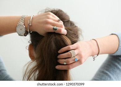 Beautiful young woman with stylish bijouterie doing her hair on white background
